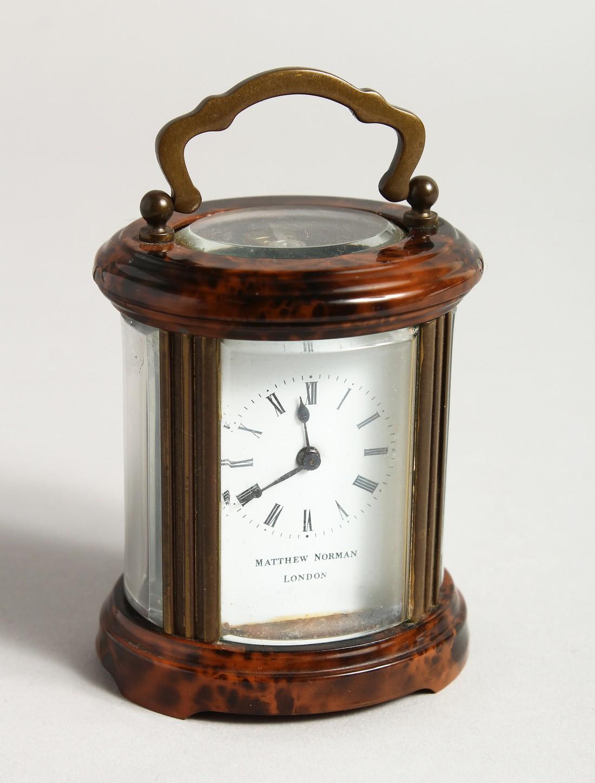 A GOOD CIRCULAR BRASS CARRIAGE CLOCK, MATTHEW NORMAN, LONDON. 3ins high