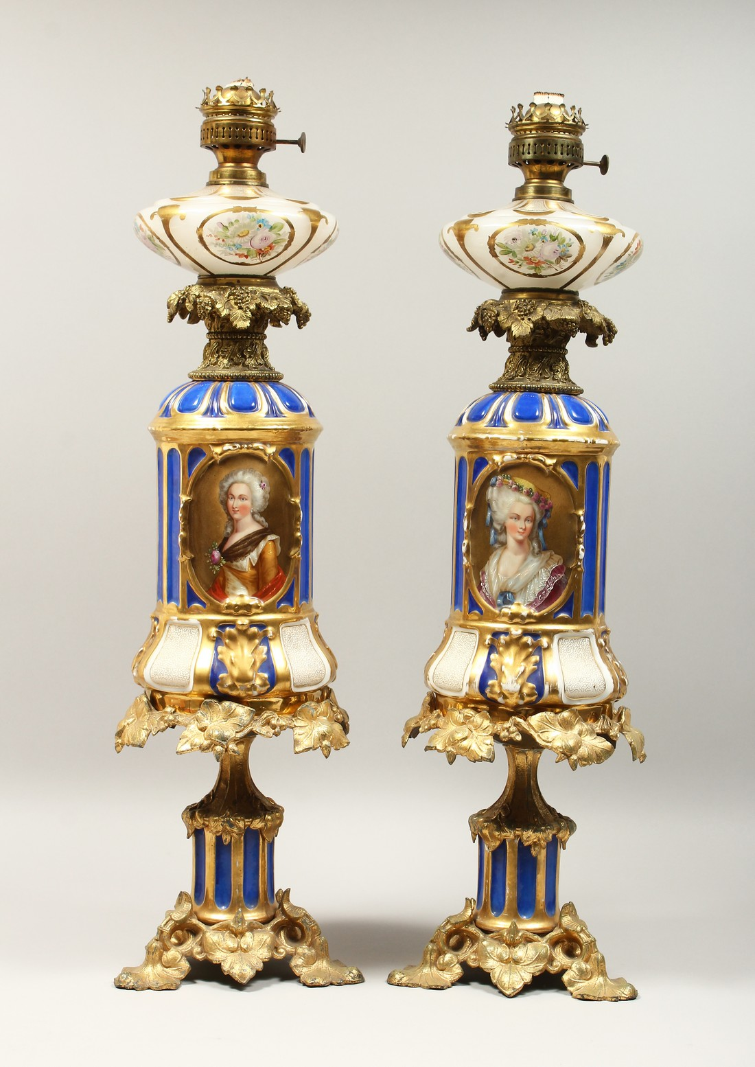 A SUPERB PAIR OF 19TH CENTURY FRENCH PORCELAIN AND GILT BRONZE LAMPS ON STANDS, painted with