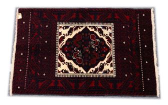 A PERSIAN RUG, 20th Century red ground with a central cream ground panel with stylised decoration.