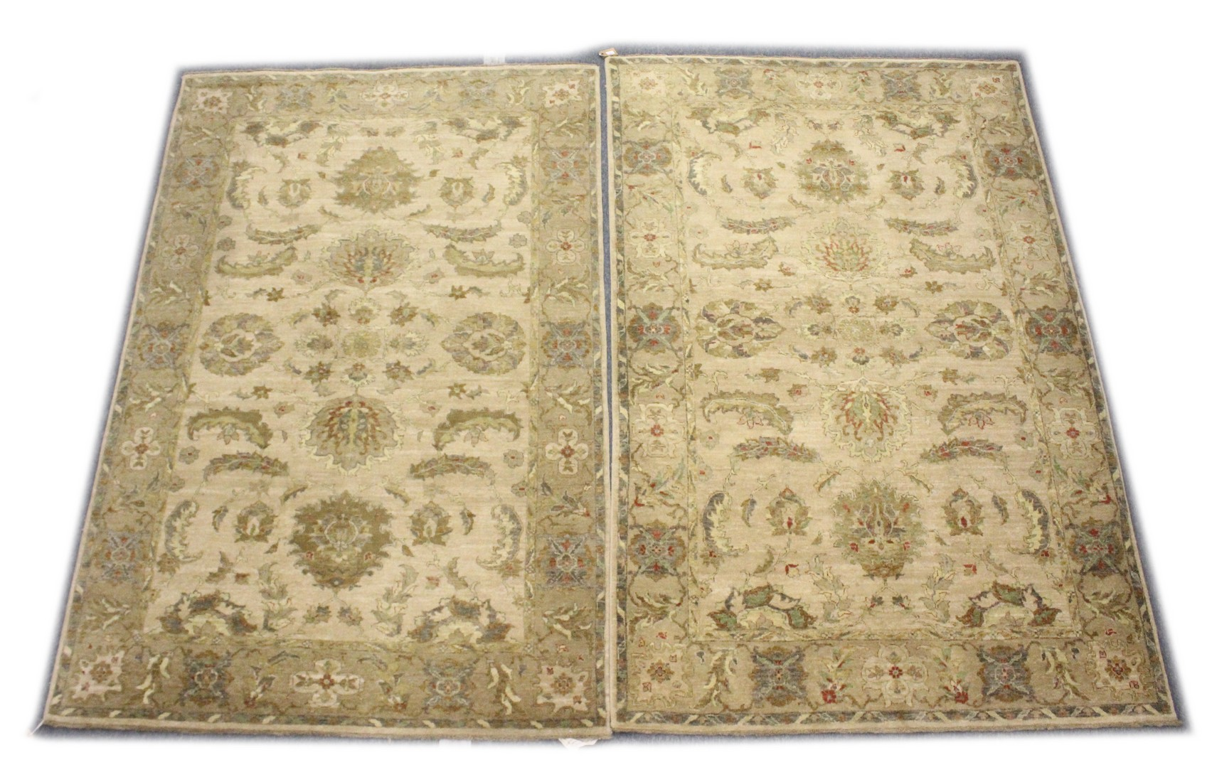A PAIR OF INDIAN CARPETS, 20TH CENTURY, beige ground with stylised leaf and flowers decoration 8ft