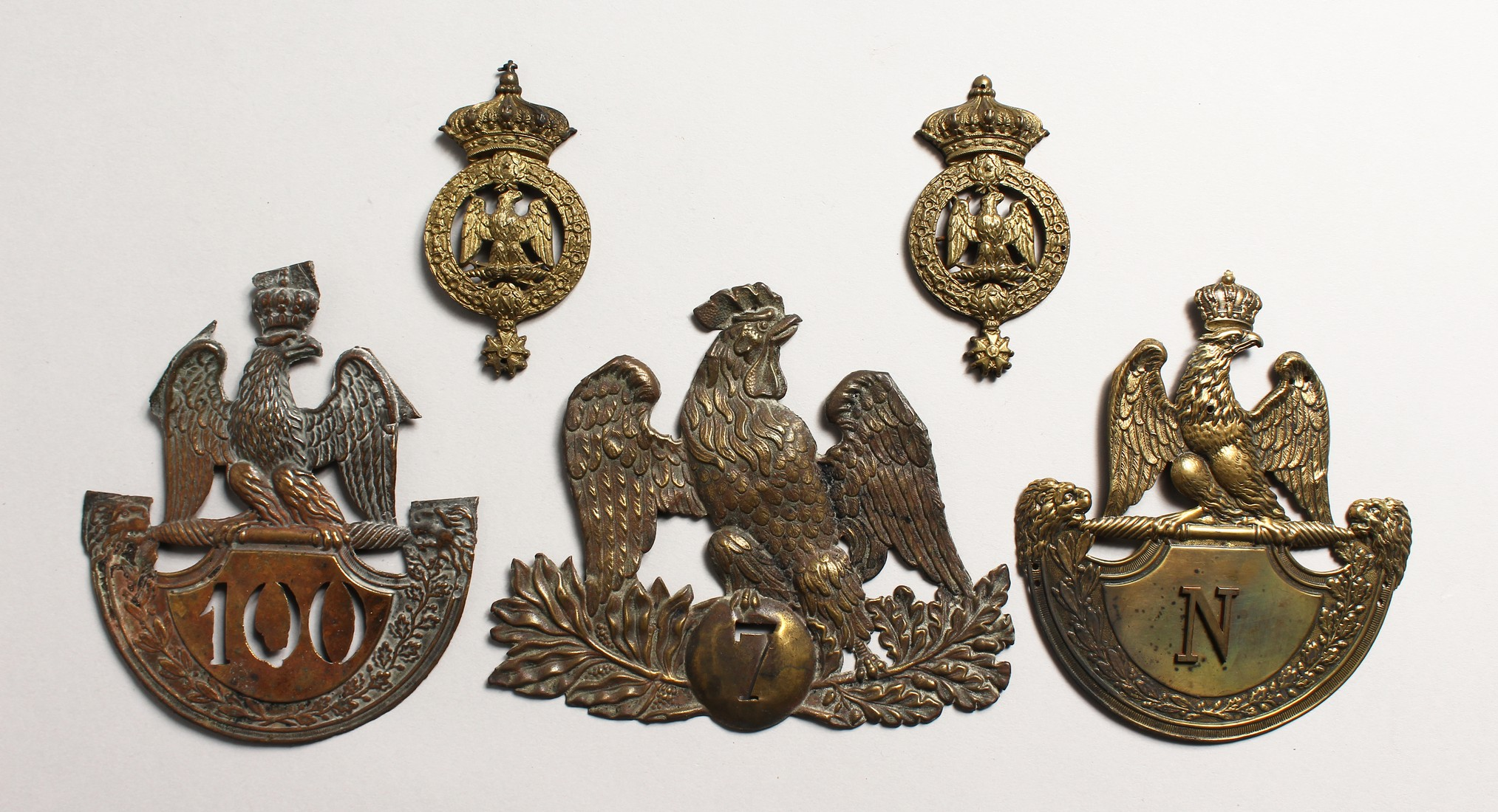 THREE LARGE NAPOLEONIC BRASS BADGES and two small badges. (5)