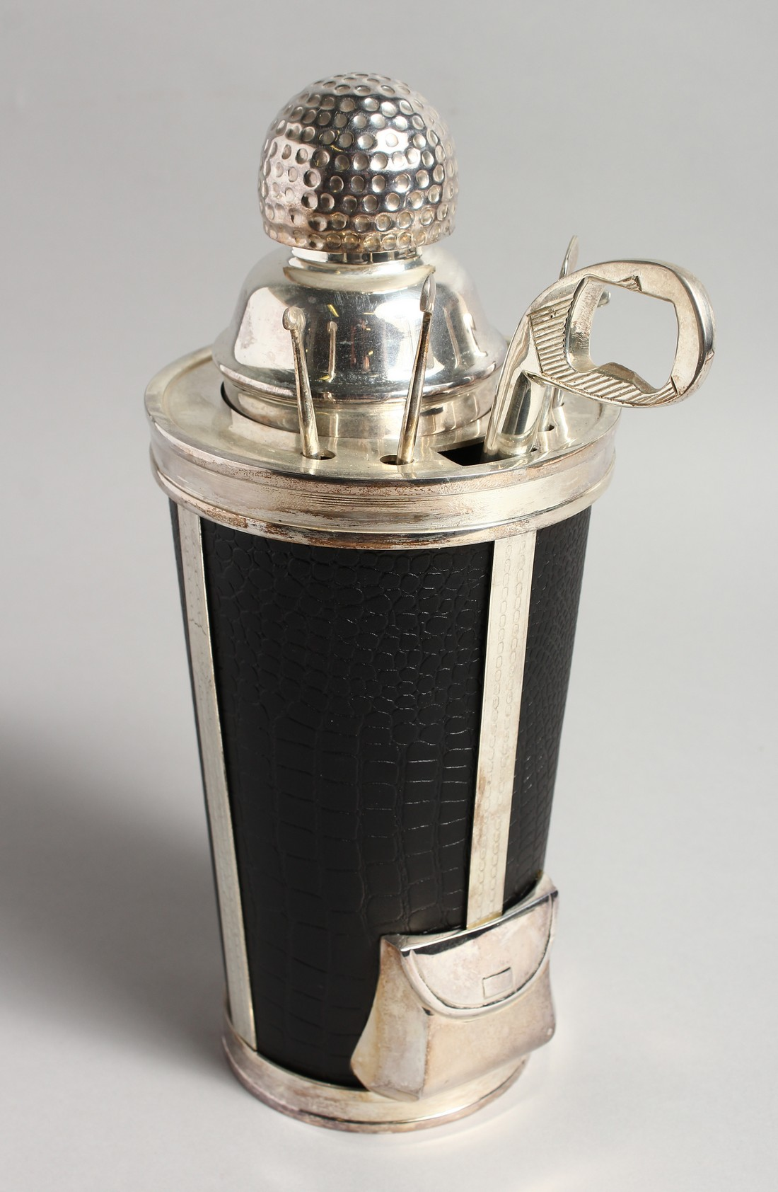 A SILVER PLATE AND LEATHER COVERED GOLF BAG COCKTAIL SHAKER with carrying handle. 11.5ins high.