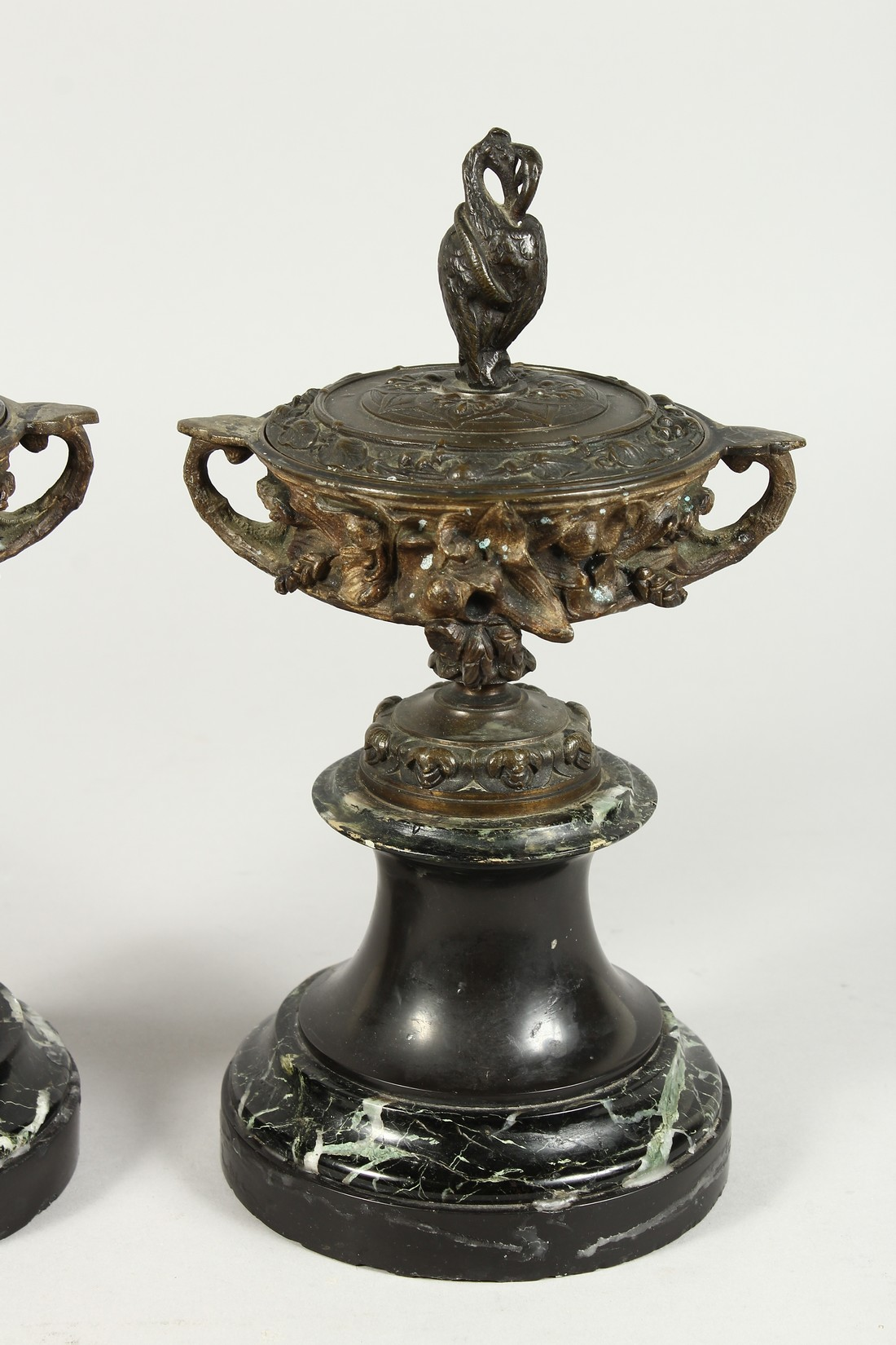 A PAIR OF BRONZE TWO HANDLED URNS AND COVERS on circular marble bases. 10ins high. - Image 3 of 6