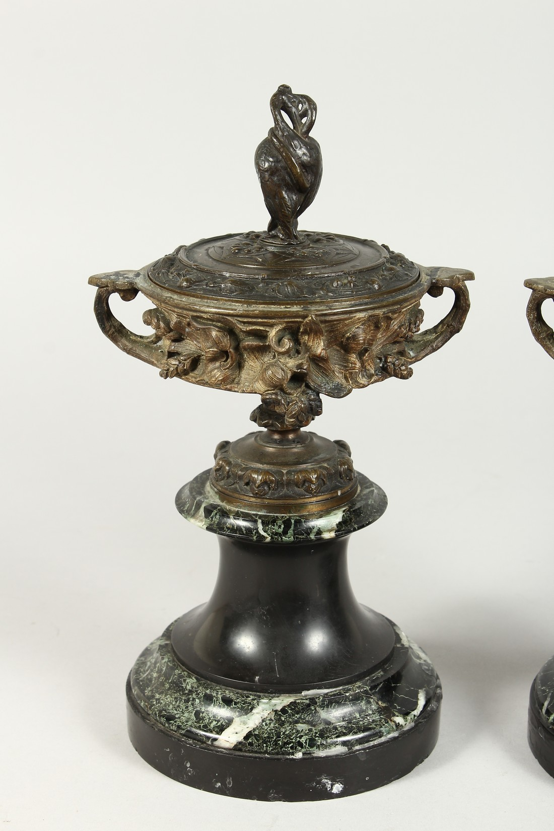 A PAIR OF BRONZE TWO HANDLED URNS AND COVERS on circular marble bases. 10ins high. - Image 2 of 6