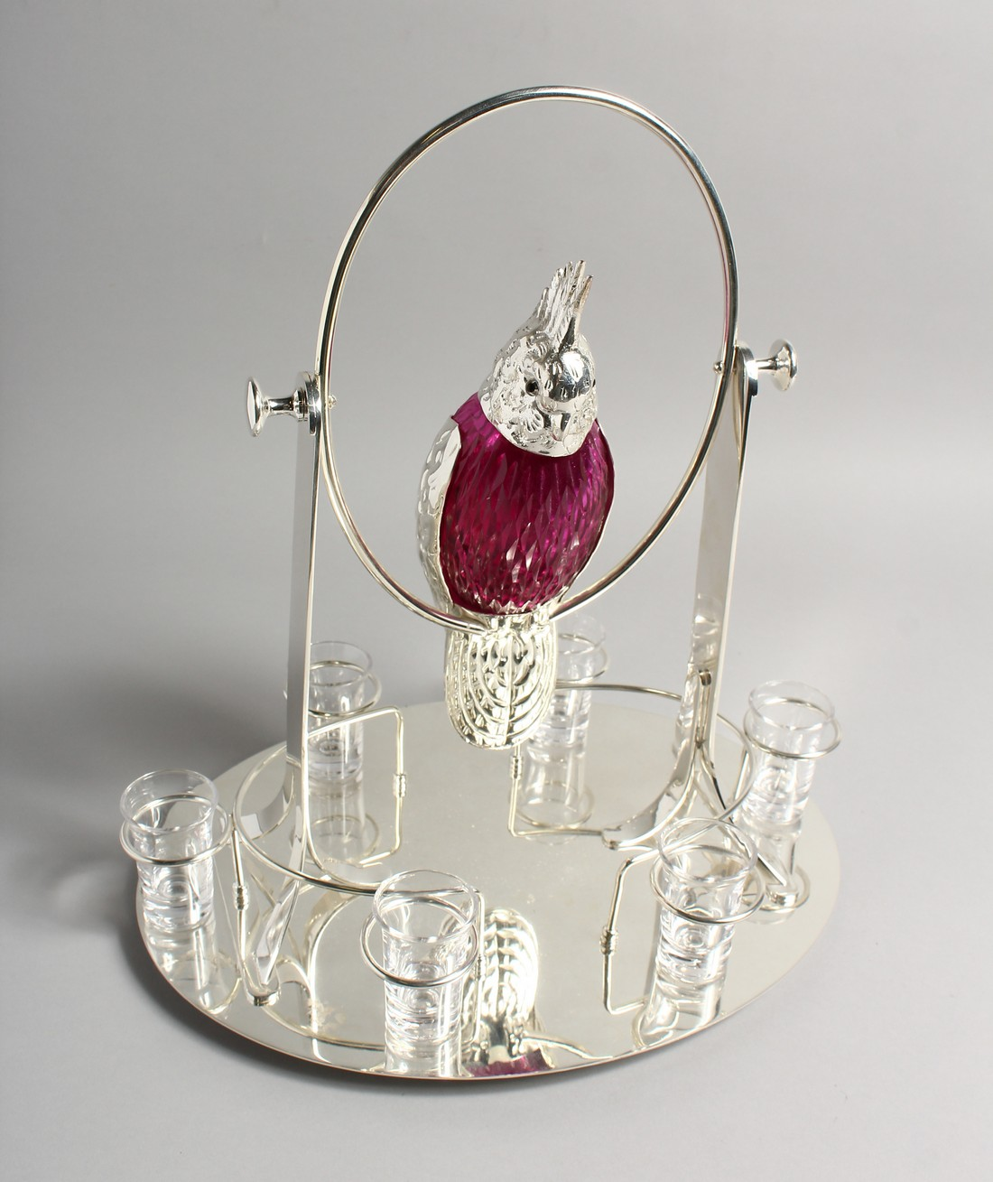 AN UNUSUAL LIQUEUR SET, the decanter modelled as a parrot on a swing, with six shot glasses to the