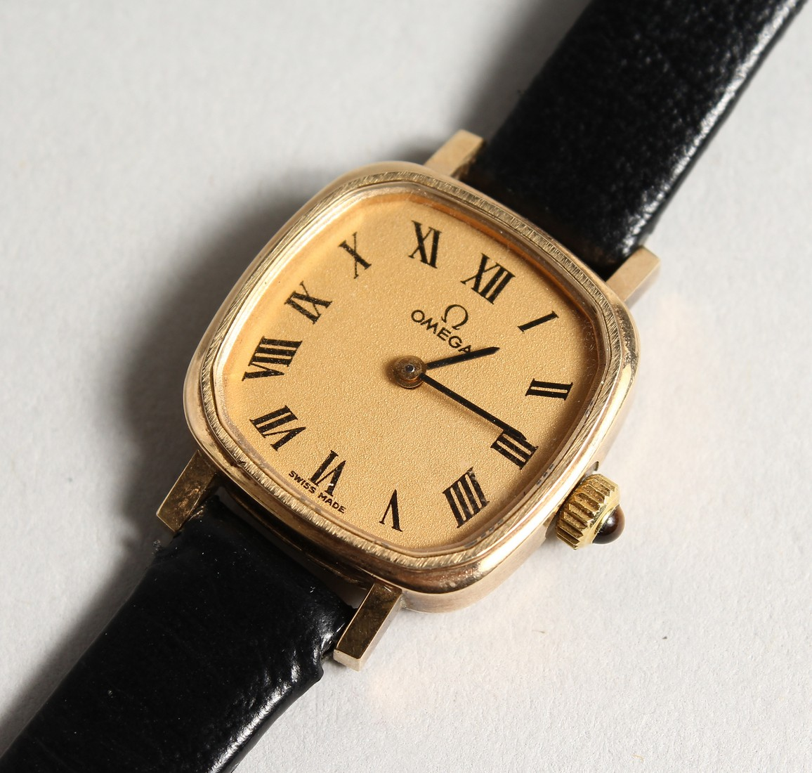 A LADIES VERY GOOD GOLD OMEGA WRIST WATCH with leather strap.