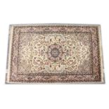 A KASHMIRI WOOL RUG, mid 20th Century, cream ground with floral decoration. 7ft 1in x 4ft 6ins