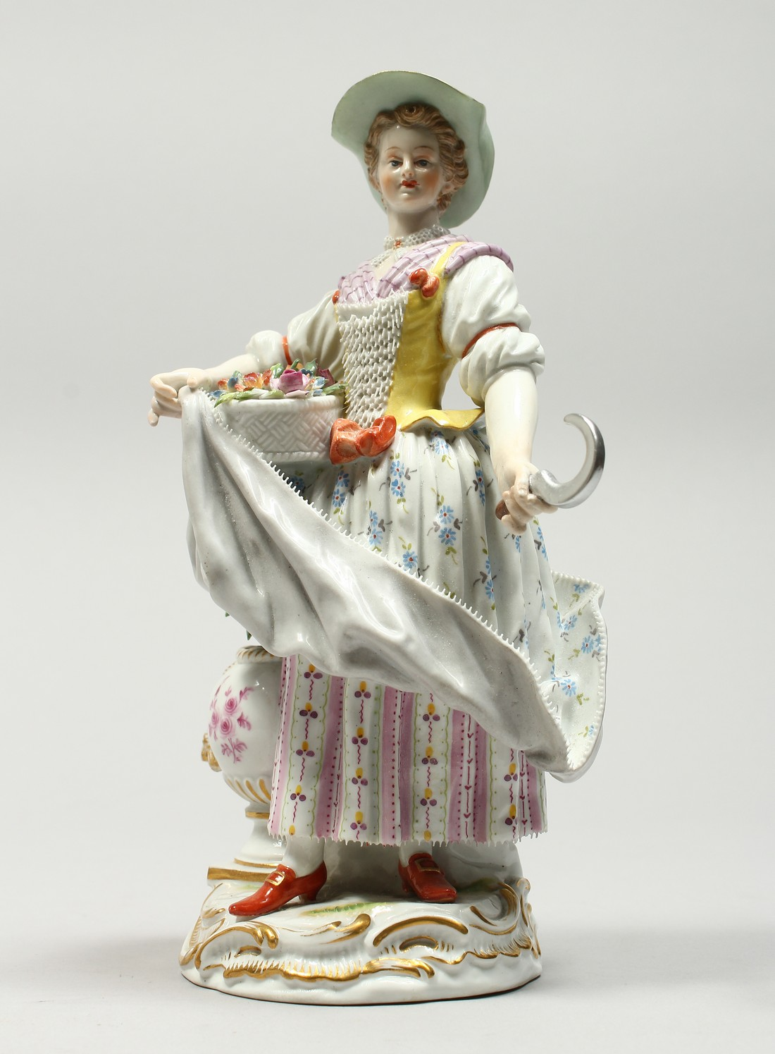 A GOOD MEISSEN PORCELAIN FIGURE OF A GARDENERESE, holding a sickle, carrying a basket of flowers, an