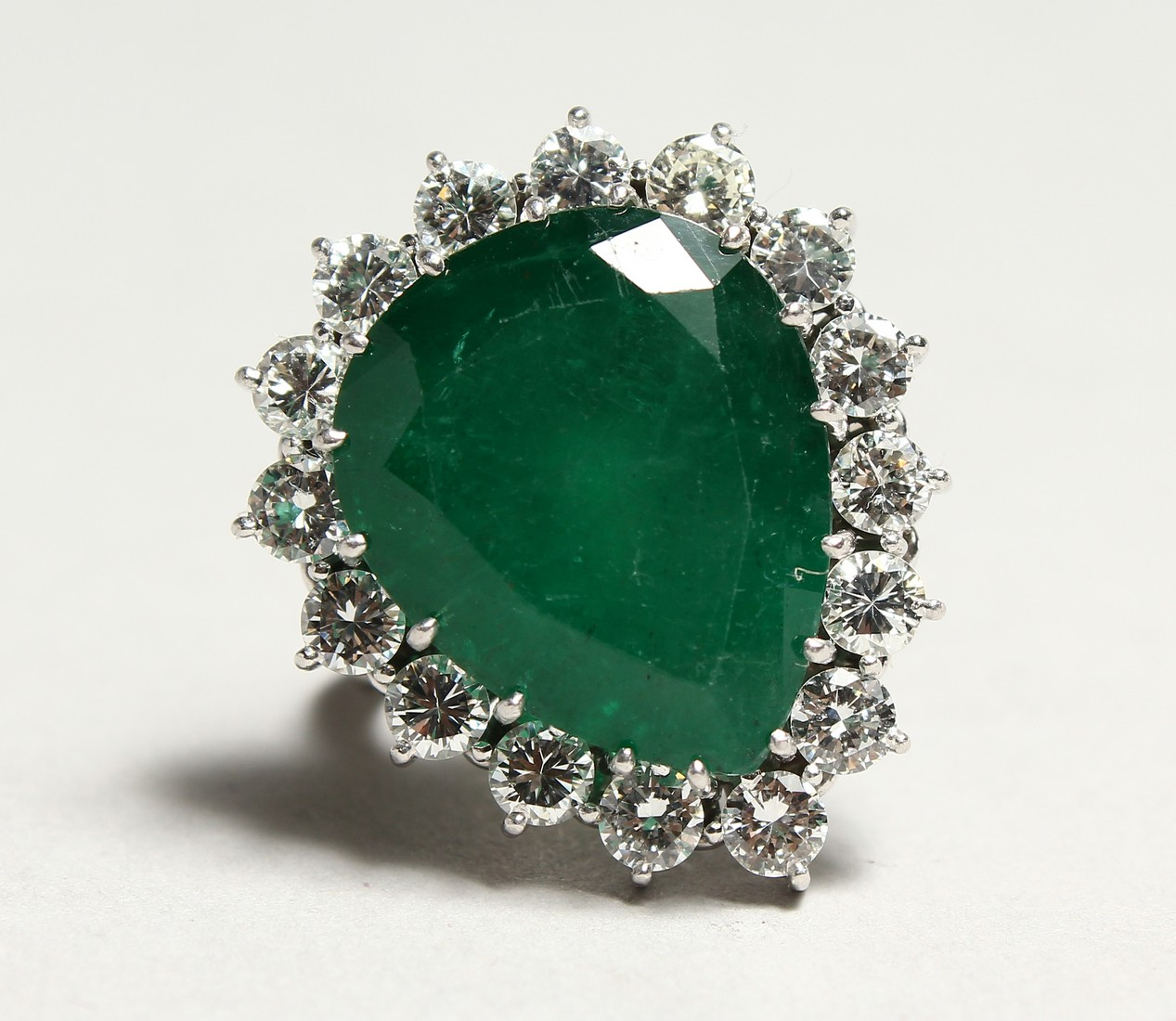 A SUPERB 18CT WHITE GOLD TIER DROP EMERALD AND DIAMOND RING set with a large emerald surrounded by