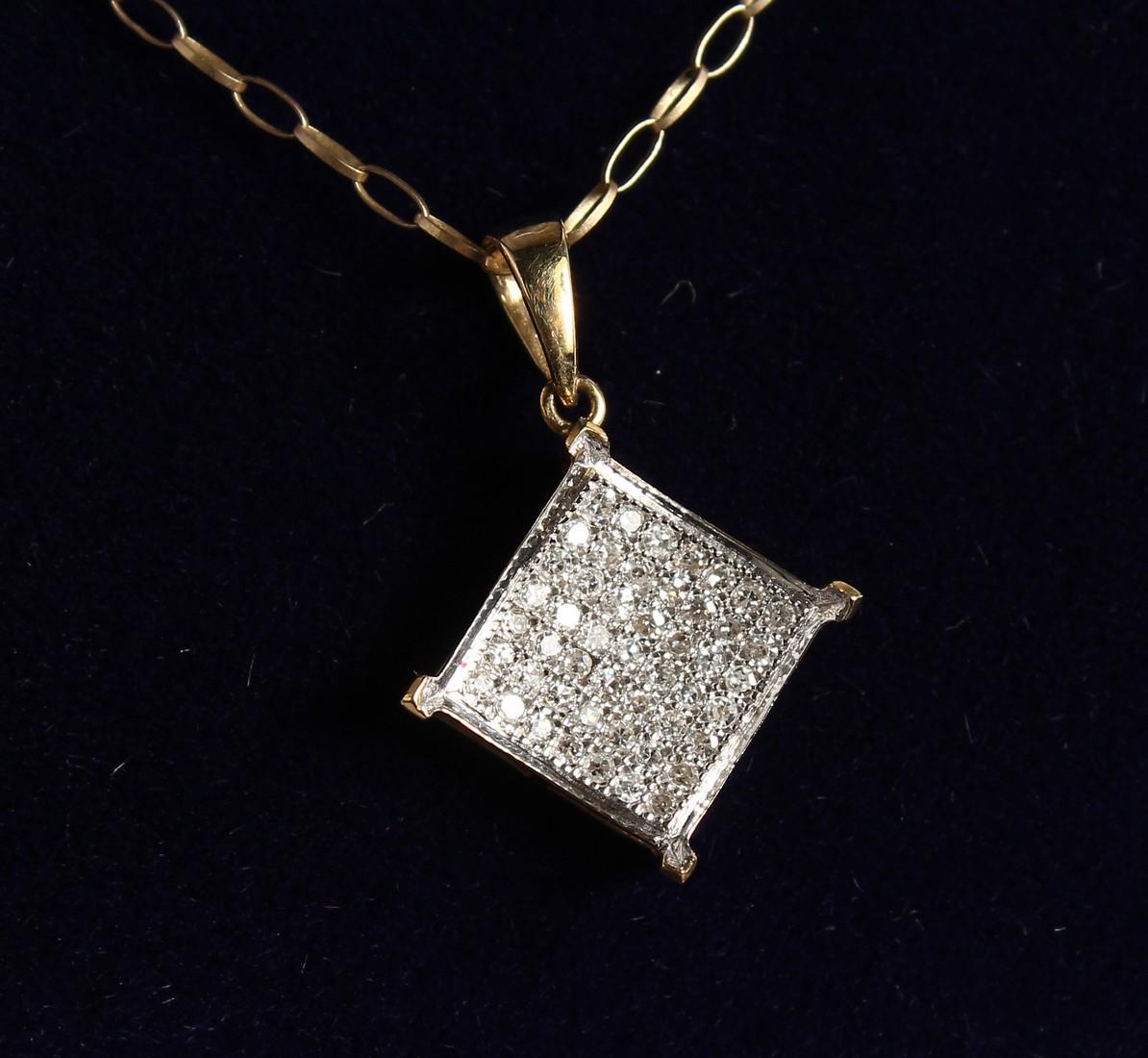 A 9CT GOLD AD DIAMOND PENDANT on a chain.