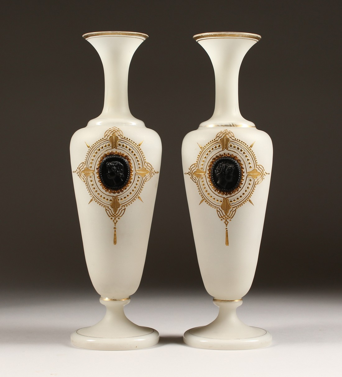 A PAIR OF CAMEO CLASSIC FROSTED VASES with a black cameo with gilt decorations 12ins high.
