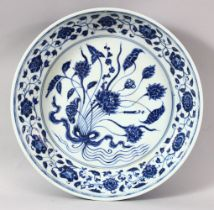 A LARGE CHINESE BLUE AND WHITE DISH, painted with flowers, with six character mark to the side, 32cm