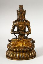 A CHINESE GILT BRONZE FIGURE OF BUDDHA / DEITY - in a seated pose holding a ball, 18cm