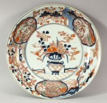 A JAPANESE IMARI / ARITA PORCELAIN DISH, painted with a vase and flowers, the border with lion dogs,