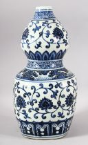 A CHINESE BLUE AND WHITE DOUBLE GOURD VASE, painted with lotus flowers, six character mark to rim,