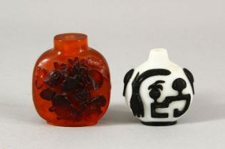 TWO CHINESE SNUFF BOTTLES - one with a white ground with black overlay, the other with carved relief