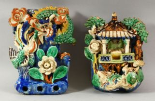 TWO CHINESE POLYCHROME POTTERY WALL POCKETS, carved with a shrine and flora with ducks / birds, 20cm