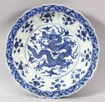 A GOOD LARGE CHINESE BLUE AND WHITE DRAGON DISH, the centre painted with a dragon amongst stylised