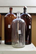 Two large amber glass chemist jars and a similar clear glass jar.