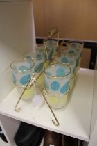 A 1970's set of eight lemonade glasses with glass carrier.