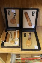 Four small Japanese models of musical instruments and two Japanese combs.