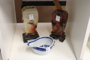 A Chinese porcelain sauceboat and two Chinese soapstone vases on stands (AF).