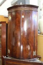 A 19th century mahogany bowfront hanging corner cupboard.