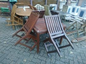 A small square garden table and four chairs.