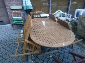 An extending garden table with six chairs and a parasol.