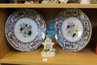 A pair of decorative plates, a porcelain figure and a frosted glass scent bottle.
