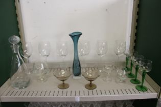 A modern glass decanter, a stylish glass vase and other glassware.