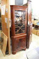 A mahogany standing corner cabinet.