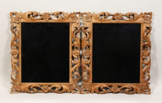 A PAIR OF 19TH CENTURY MIRRORS with leaf and flower carved wood frames 22ins x 19ins