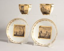 TWO PAIRS OF, POSSIBLY FRENCH, CUPS AND SAUCERS with panels of buildings.