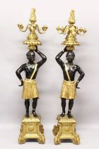 A SUPERB LARGE PAIR OF 19TH CENTURY STANDING NUBILE FIGURE CANDELABRAS formed as a a pair of African