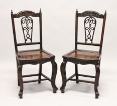A GOOD PAIR OF 19TH CENTURY REDWOOD CHINESE CHAIRS with pierced backs and solid seats on curving