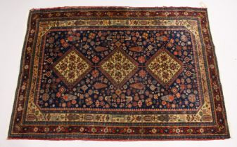 A PERSIAN QUASHQI CARPET, dark blue ground with three central diamond shaped medallions stylised