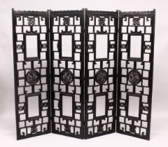 A CHINESE BLACK LACQUER FOUR SECTION CARVED WOOD FOLDING DRESSING SCREEN. Each panel 5ft 3ins high x