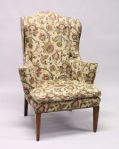 A GEORGIAN STYLE MAHOGANY WING ARM CHAIR with loose cushions on tapering legs.