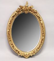 A DECORATIVE GILT FRAMED OVAL WALL MIRROR 3ft 7ins high x 2ft 6ins wide