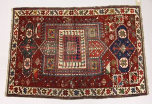 AN UNUSUAL SMALL CAUSASIAN SHIRWAN RUG, claret ground with stylised design. 4ft 2ins x 2ft 10ins