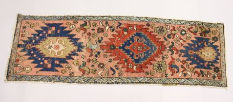 A SMALL HERIZ RUNNER, pink ground with three medallions 5ft 10ins x 1ft 11ins.