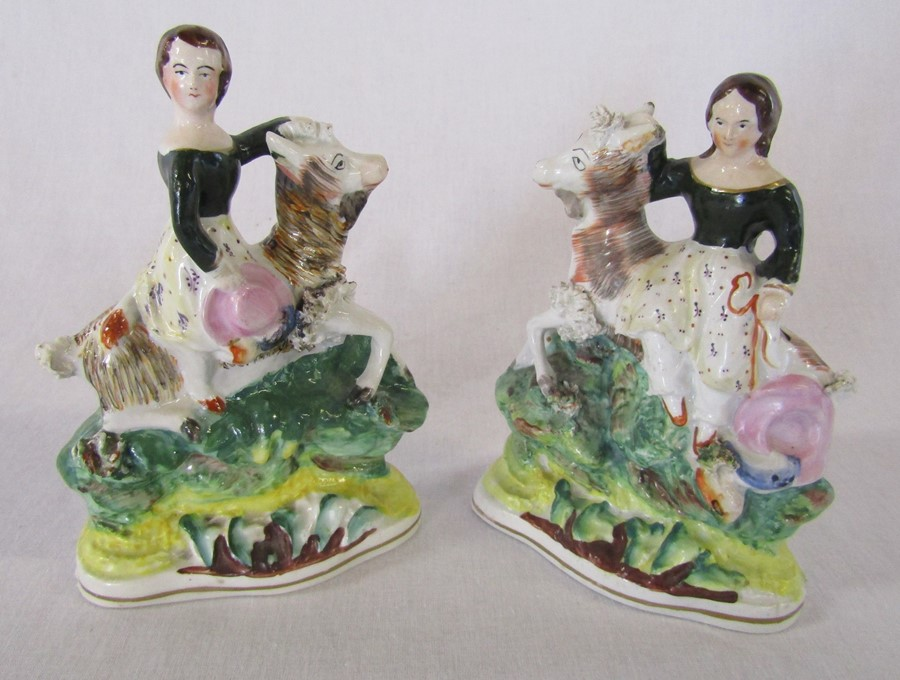 Pair of Staffordshire flatback figures of children / young girls riding goats possibly with some