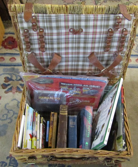 Wicker picnic hamper containing various books inc Harry Potter, The Home Workshop, Bleak House and
