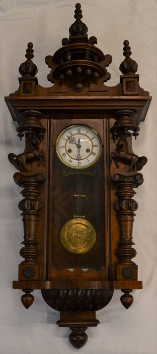 Vienna regulator wall clock with a 2 train spring driven mechanism in a mahogany case flanked by 2