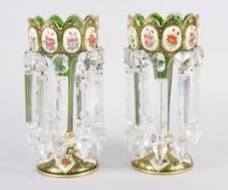 A pair of green glass lustres with gilt and floral panel decoration, hung cut glass spear point