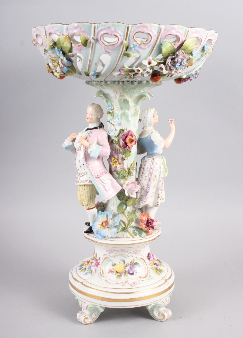 A Continental porcelain table centre, the stem decorated with two figures and floral decoration to