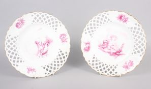"""A pair of bone china plates with puce cherub and floral decoration with pierced borders, 9 1/2"""" dia"""
