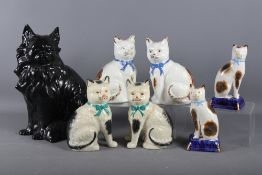 """A black glazed model of a cat, 13"""" high, and three other pairs of model cats"""