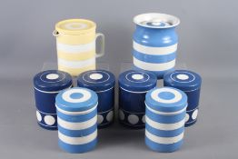 Seven Cornishware blue and white storage jars, and a yellow and white Cornishware jug and cover,